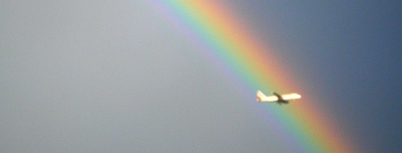 Airliner flying in front of rainbow